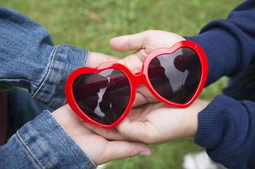 Children holding red heart glasses