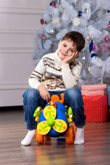 boy with Christmas gift, boy in festive costume near the Christm