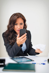 Angry businesswoman with phone in office.