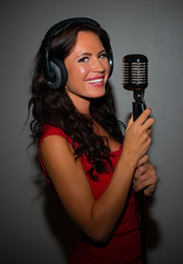 Attractive brunette woman recording a song in music studio.