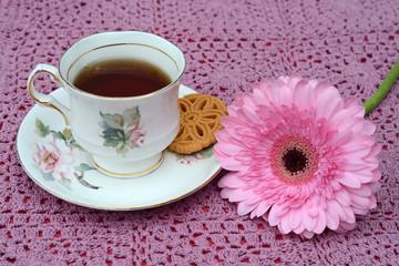Koffie of thee in een oud kopje en een gehaakt kleedje