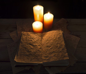Open black magic book with candles