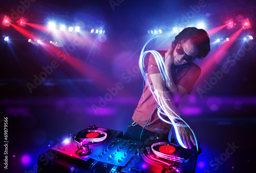 Disc jockey playing music with light beam effects on stage - 69879566