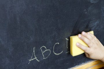 Child's hand cleans letters abc education background concept
