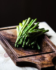 Bunch of fresh green asparagus spears tied with twine on a rusti
