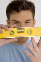 Junger Mann mit gelben Wasserwaage,close-up
