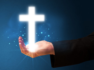 Glowing cross in the hand of a businessman