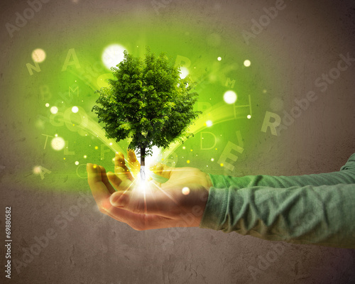 canvas print picture Glowing tree growing in the hand of a woman