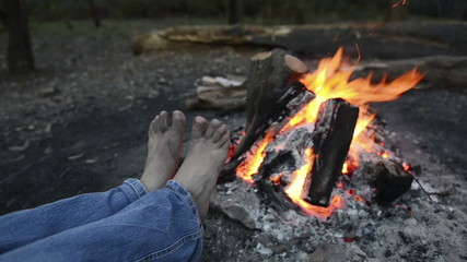 Person warms their feet next to a campfire at dusk
