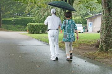 小雨の中をウォーキングするシニア夫婦