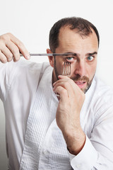 Man cutting his eyes with knife and fork