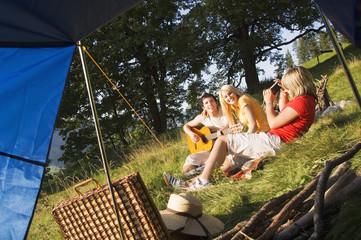 Drei junge Leute mit Picknick,Frau,die Foto