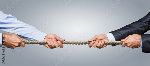 Tug war, two businessman pulling a rope in opposite directions - 69881374