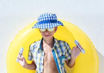 Funny child with sunglasses and panama on summer vacation