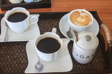 cappuccino and black  coffee on wooden table