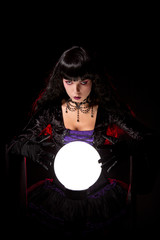 Beautiful witch or fortune teller with a crystal ball