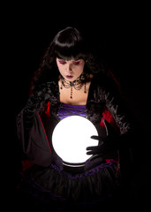 Attractive witch or fortune teller looking into a crystal ball