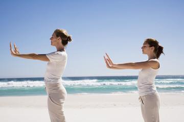 Zwei Frauen,die Ausübung von Yoga am Strand,Seitenansicht