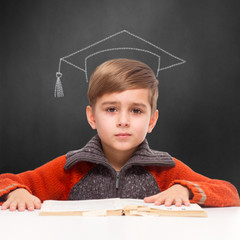 child learning with mortar board chalk drawing on blackboard