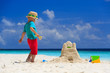 little boy playing with sand on tropical beach