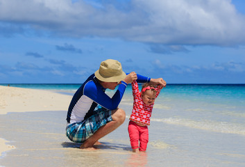 father and little daughter learning to walk on beach