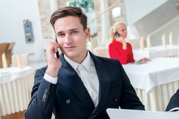 Phone call. Two successful and confident businessman sitting at