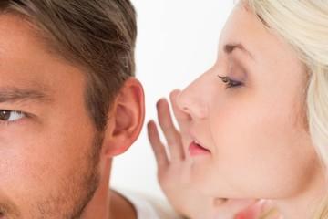 Woman whispering secret into a mans ear