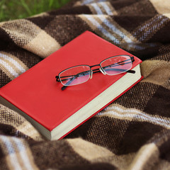 Book and glasses outdoors