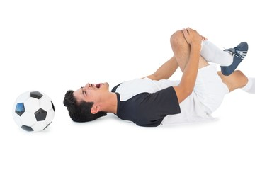 Soccer player lying down and shouting in pain