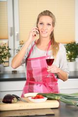 Frau in Küche mit Weinglas