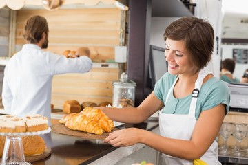 Pretty waitress holding tray of croissants
