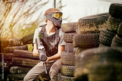 Paintball player standing  behind cover - 69885347