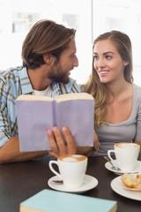 Happy couple enjoying a coffee reading a book
