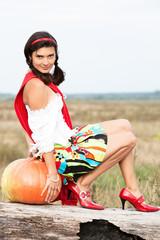 Young beautiful caucasian girl with pumpkin outdoors.