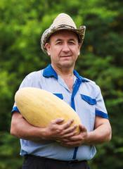 Happy gardener with melon in hands