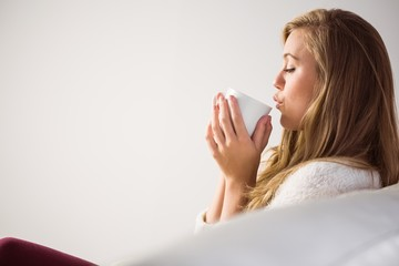 Pretty blonde relaxing on the couch with tea