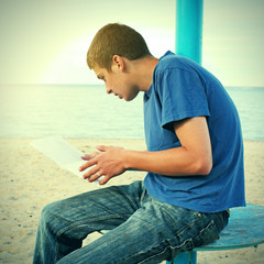 Teenager reading on the Beach
