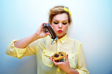 Young woman pouring chocolate sauce over dessert.