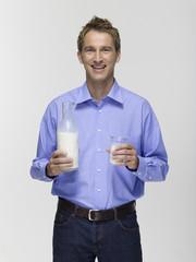 Junger Mann hält ein Glas Milch,Portrait