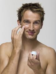Junger Mann trägt Gesichtscreme auf