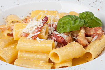 Close-up italian rigatoni plate with prosciutto, parmesan cheese