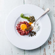 Beef tartare with capers and onion on white plate on blue backgr