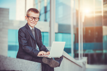happy kid businessman with laptop