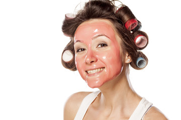 Smiling portrait of a young woman with curlers and face mask