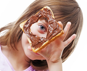 little girl looking through  bread with chocolate  butter
