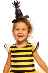 Girl in striped bee costume wearing spider hat