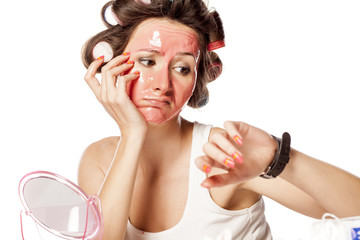 bored young woman with curlers and face mask looking at watch
