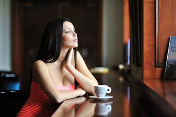 Beautiful woman sitting in the cafe with a cup of coffee