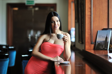 Young woman sitting in the cafe with a cup of coffee
