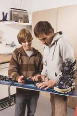Deutschland,Vater und Sohn Festsetzung Snowboard,lächelnd